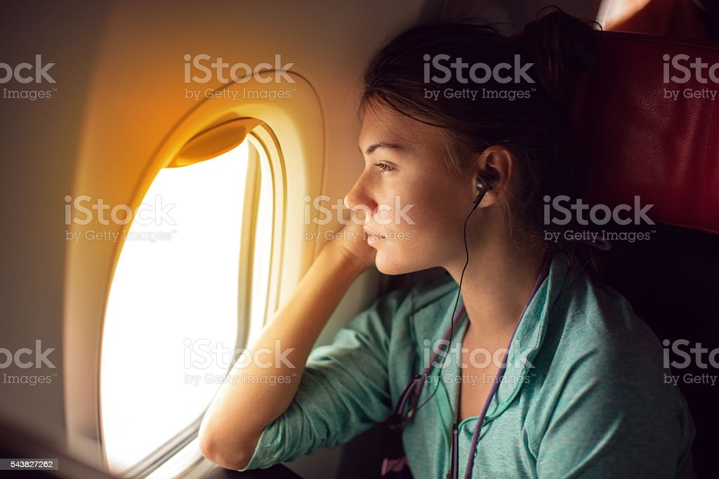 Woman traveling with plane and sitting by the window stock photo