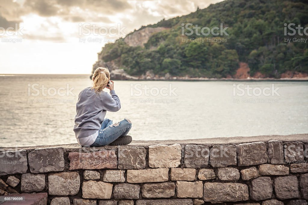 Woman traveller making mobile photo of picturesque landscape during traveling stock photo