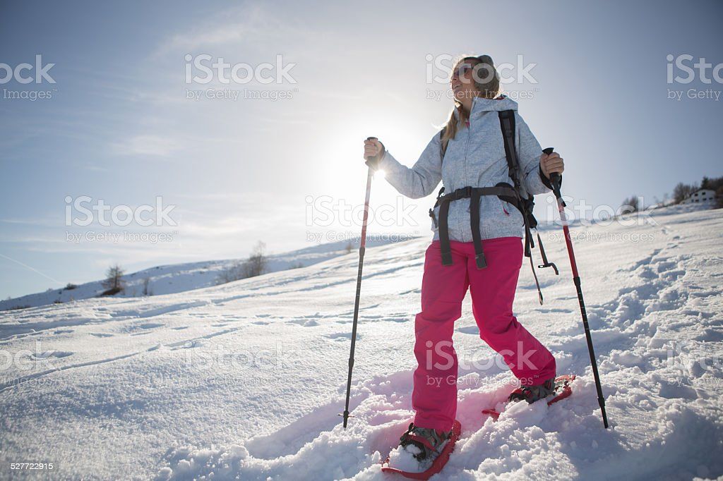 Woman trekking in winter-snowshoeing stock photo