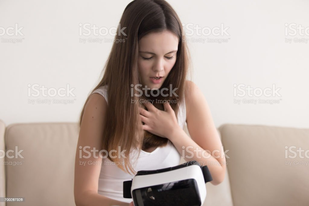 Woman tries to calm down after using VR glasses stock photo