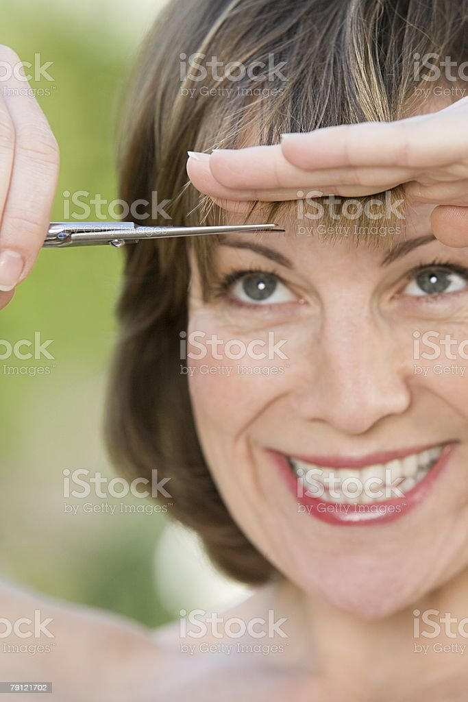 Woman trimming her fringe stock photo