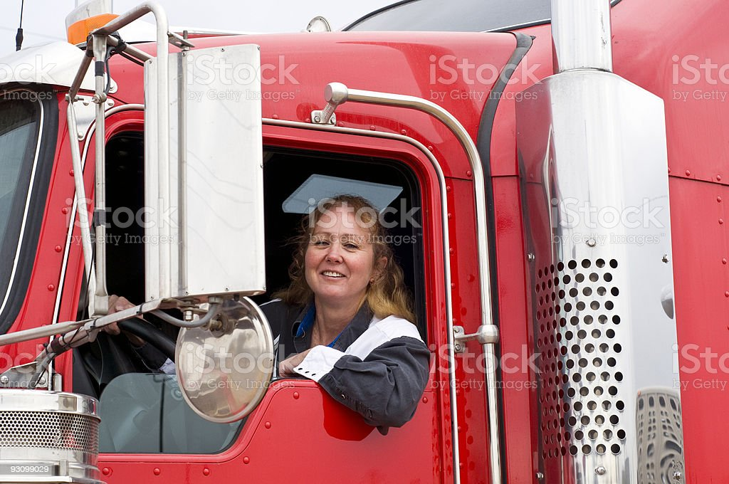 Woman truck driver looking out the window stock photo