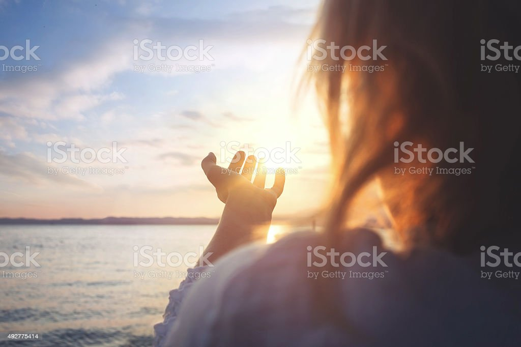 woman try to grab the sun stock photo