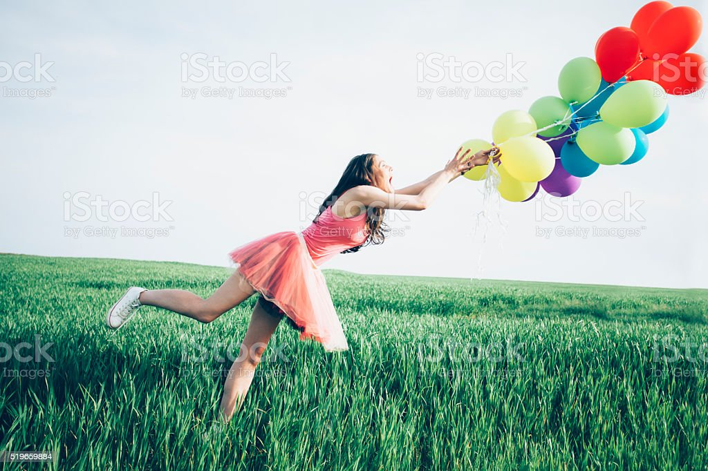 Woman try to hold balloons blown away by the wind stock photo