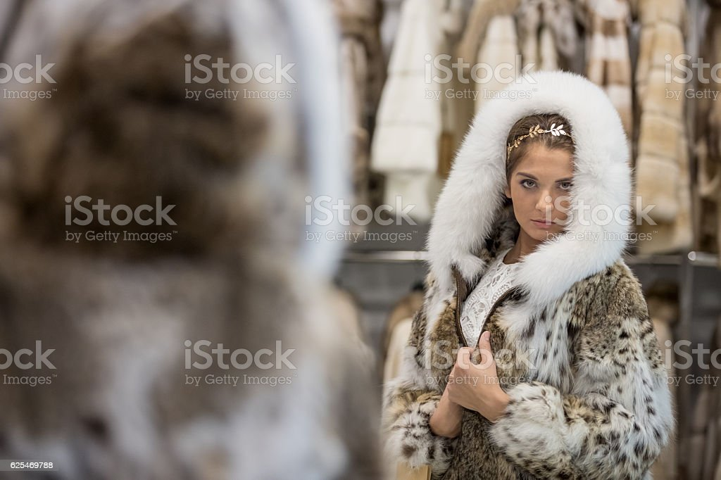 Woman trying fur coat in store stock photo