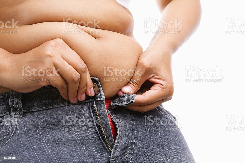 Woman trying hand to zipper her jeans stock photo