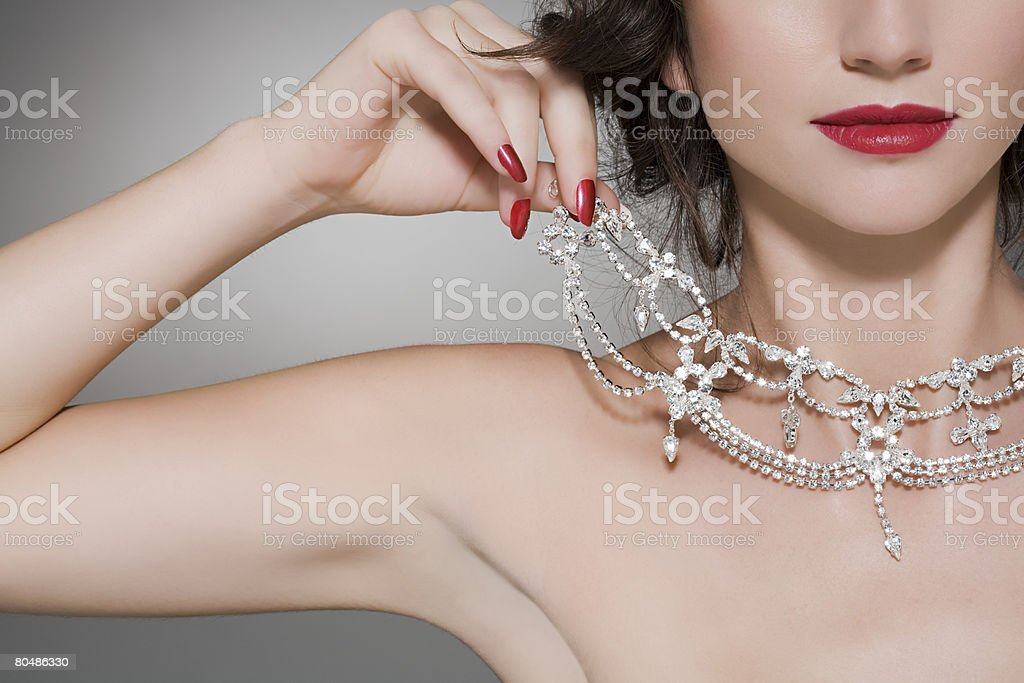 Woman trying on a diamond necklace stock photo