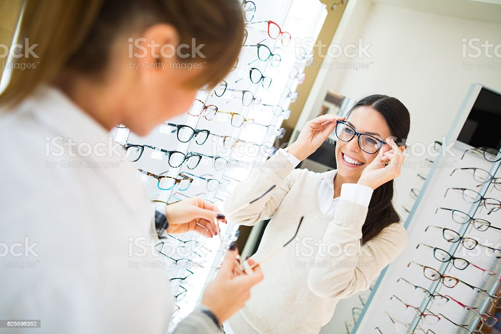 Woman trying on eyeglasses in optical shop stock photo
