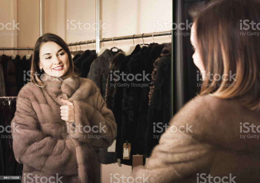 woman trying on fur coat in women's cloths store stock photo