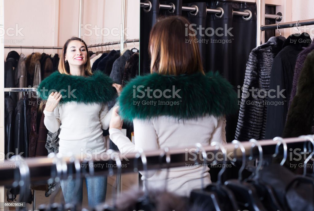 woman trying on fur neckpiece in women's cloths store stock photo