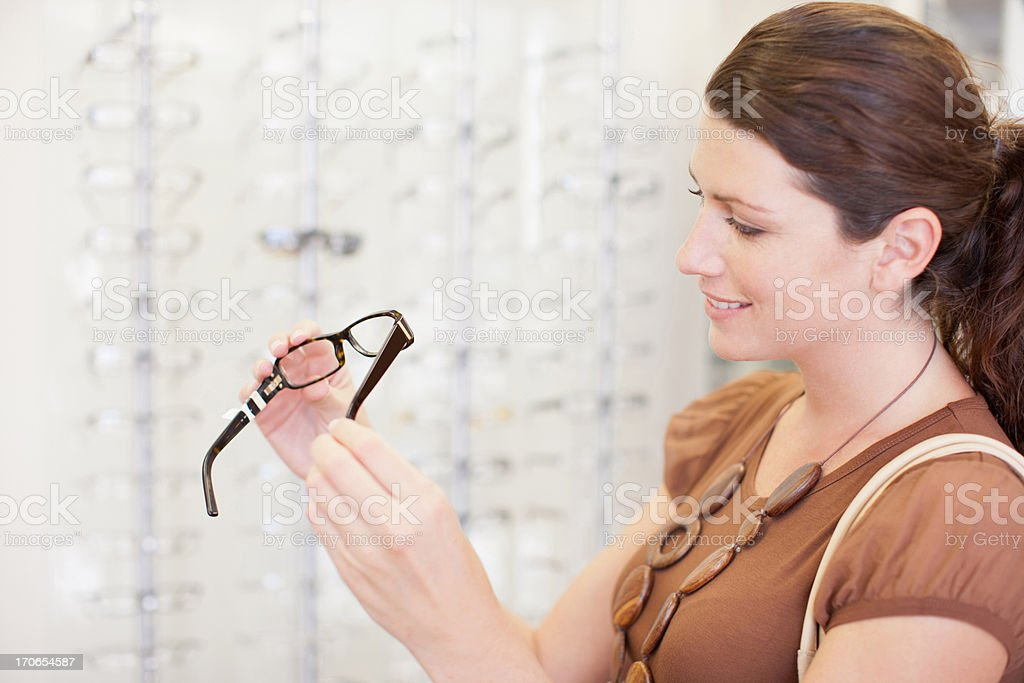 Woman trying on glasses in optometrist's shop stock photo