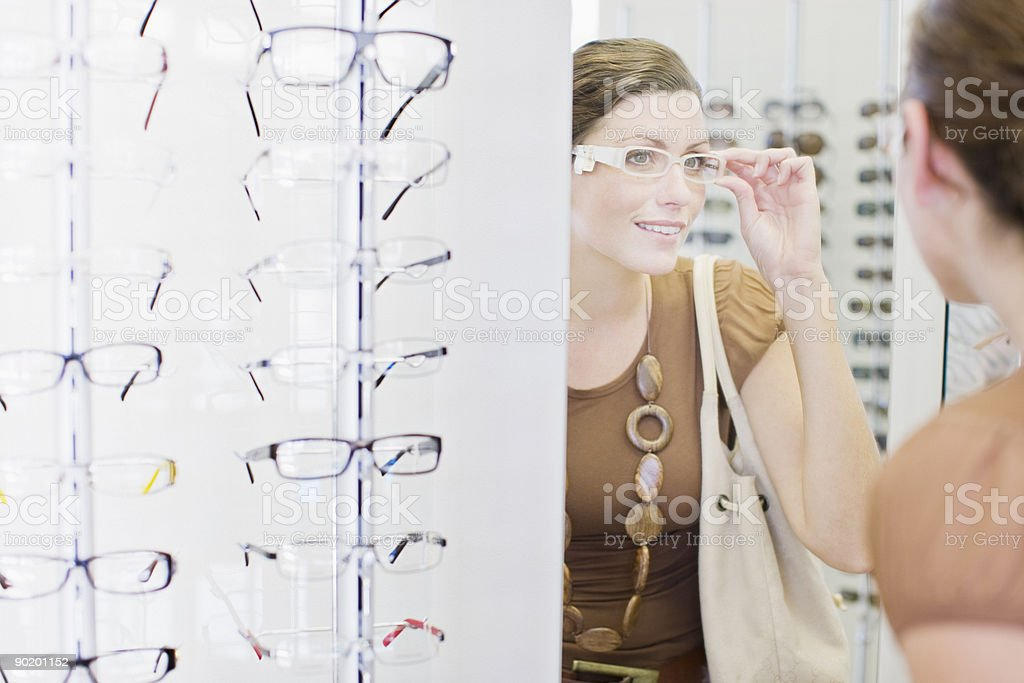 Woman trying on glasses in optometrists shop stock photo