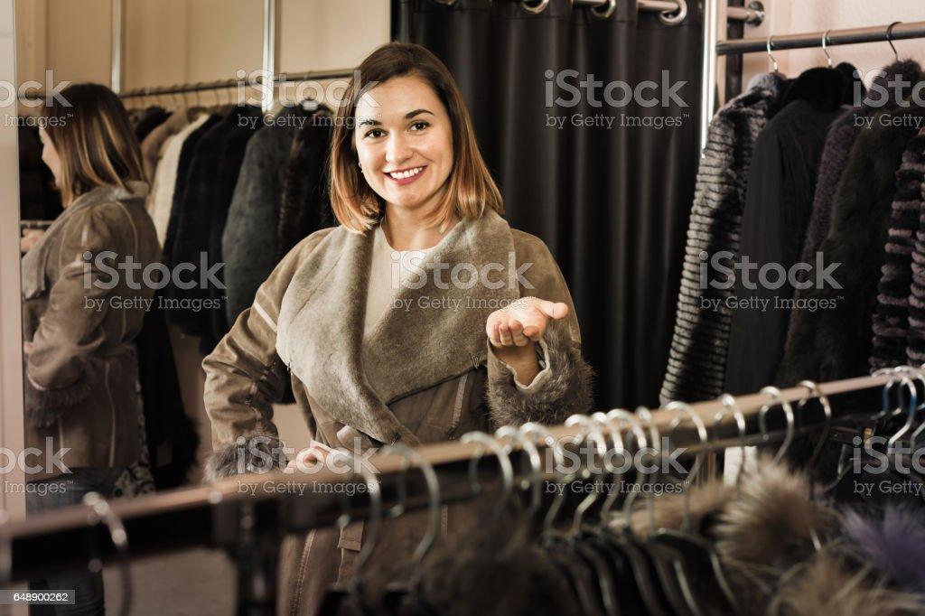 Woman trying on sheepskin coat in women's cloths store stock photo