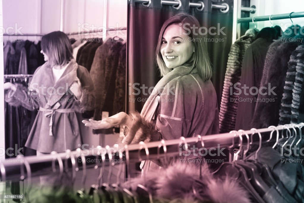 Woman trying on sheepskin coat in women's cloths store stock photo