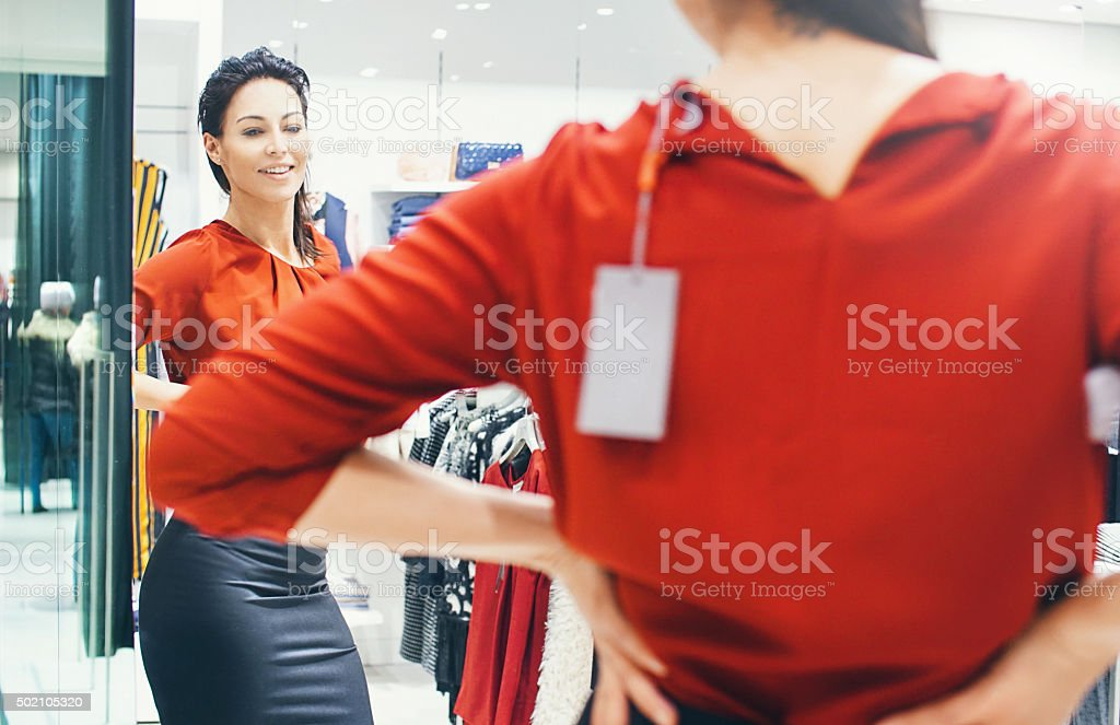 Woman trying on some clothes at a retail store. stock photo