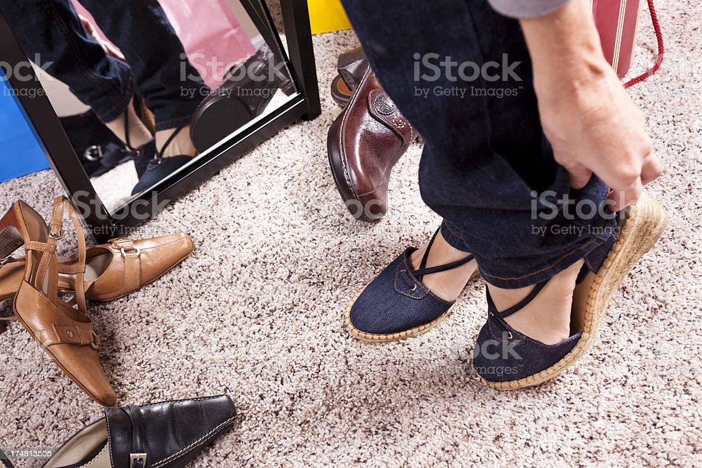Woman trying on wedge shoes and heels. Reflection in mirror. royalty-free stock photo