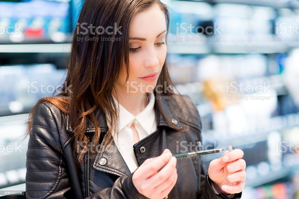 Woman trying product in a beauty shop stock photo