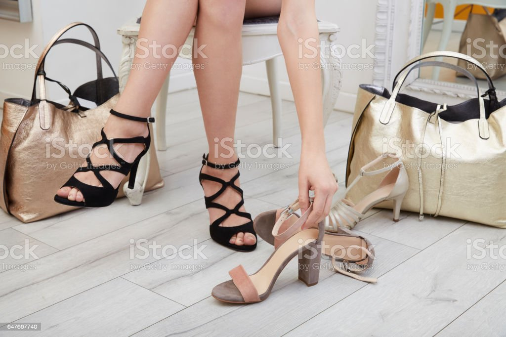 Woman trying  shoes and bags sitting in a shop stock photo