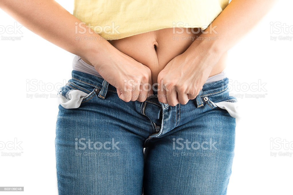 Woman trying to close jeans button with difficult from fat stock photo