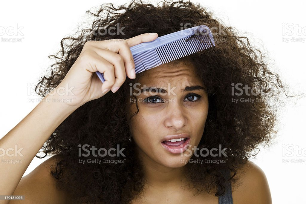 Woman trying to comb her frizzy hair stock photo