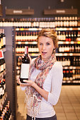 Woman trying to decide which bottle of wine to buy