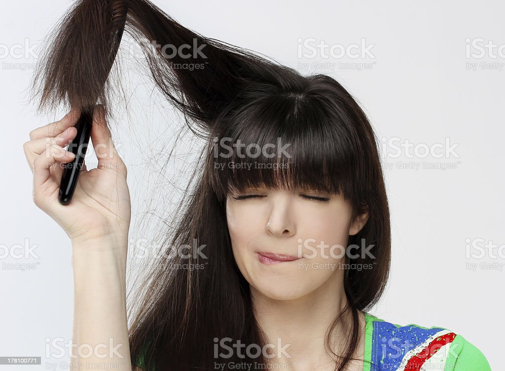 Woman  trying to get a brush out of her hair stock photo
