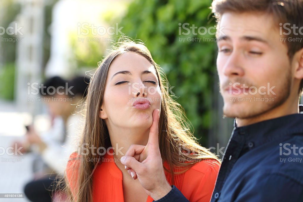 Woman trying to kiss a man and he rejects her stock photo