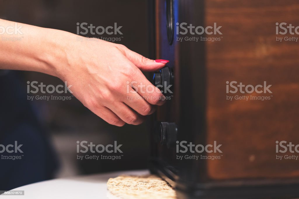 Woman tuning a station on a vintage radio stock photo