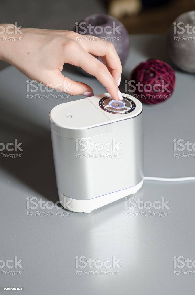 woman turn on air humidifier stock photo