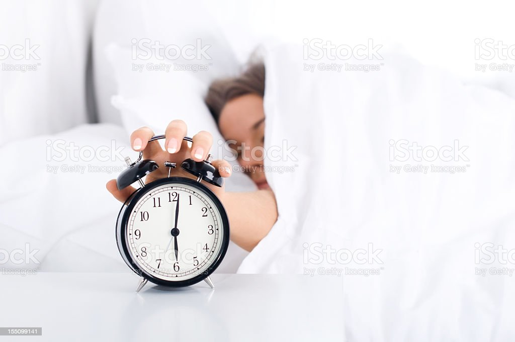 Woman turning off alarm clock from under the covers stock photo