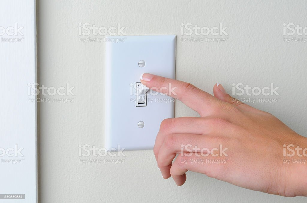 Woman turning off light switch stock photo