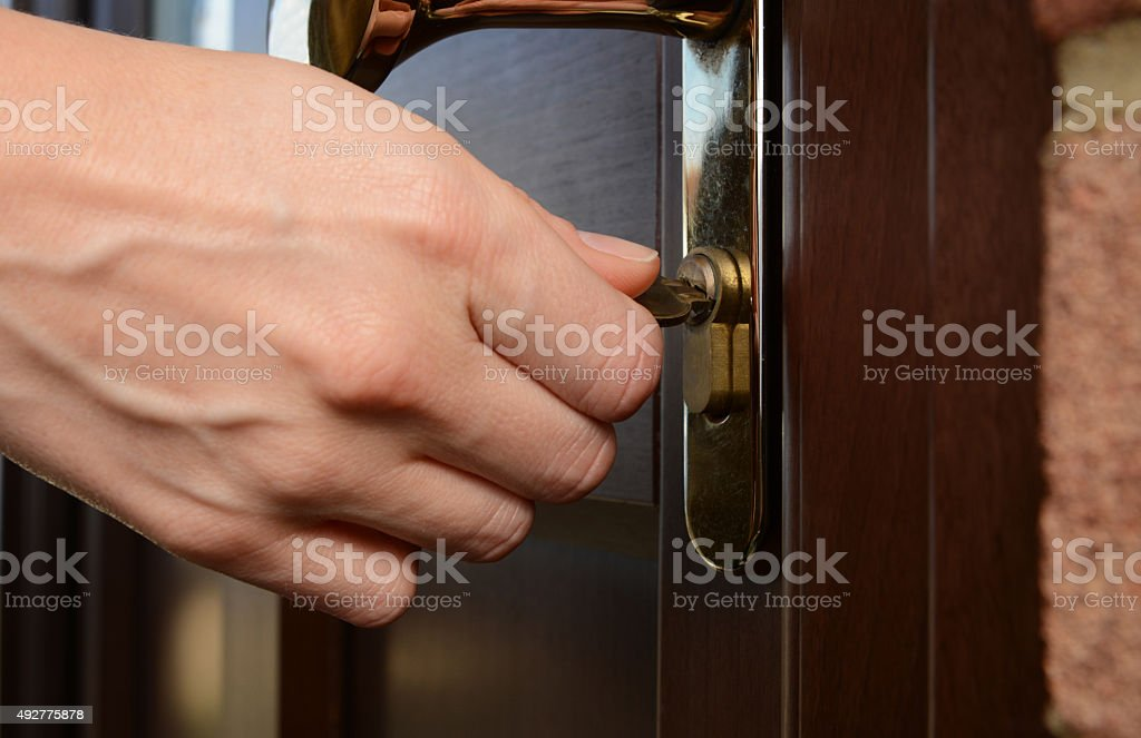 Woman turns key in a lock on an external door stock photo