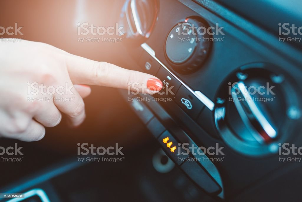Woman turns on air conditioning in her car stock photo