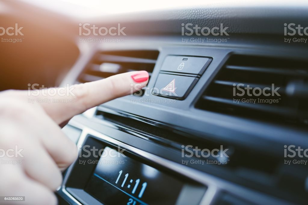 Woman turns on the emergency lights in the car. stock photo