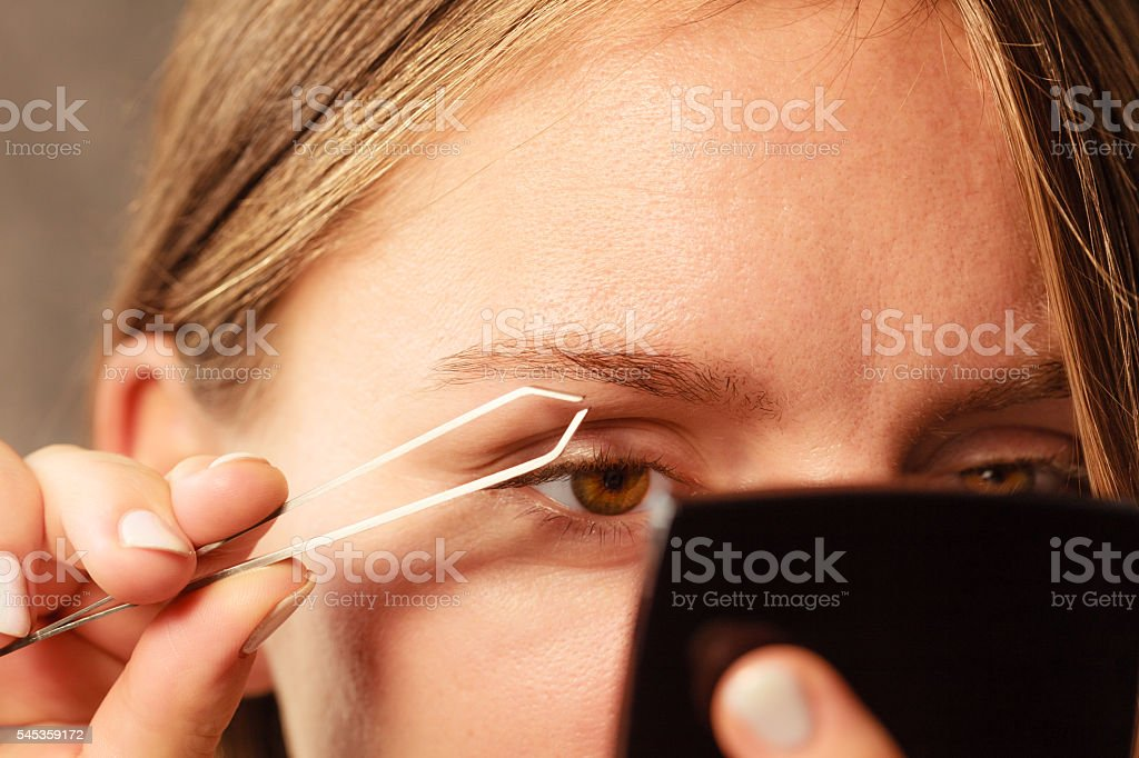 Woman tweezing eyebrows depilating with tweezers stock photo