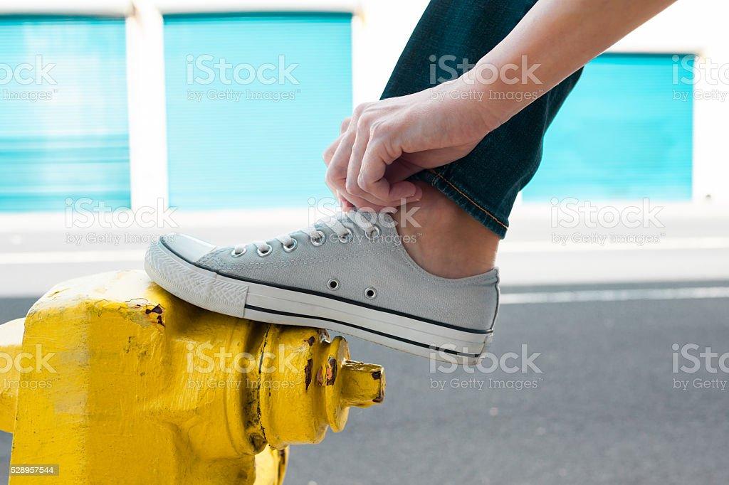 Woman tying her shoe lace stock photo