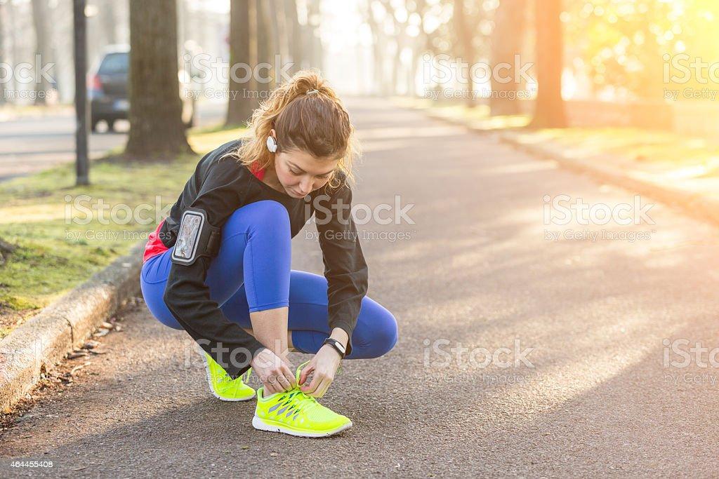 A woman tying her shoe preparing to run stock photo