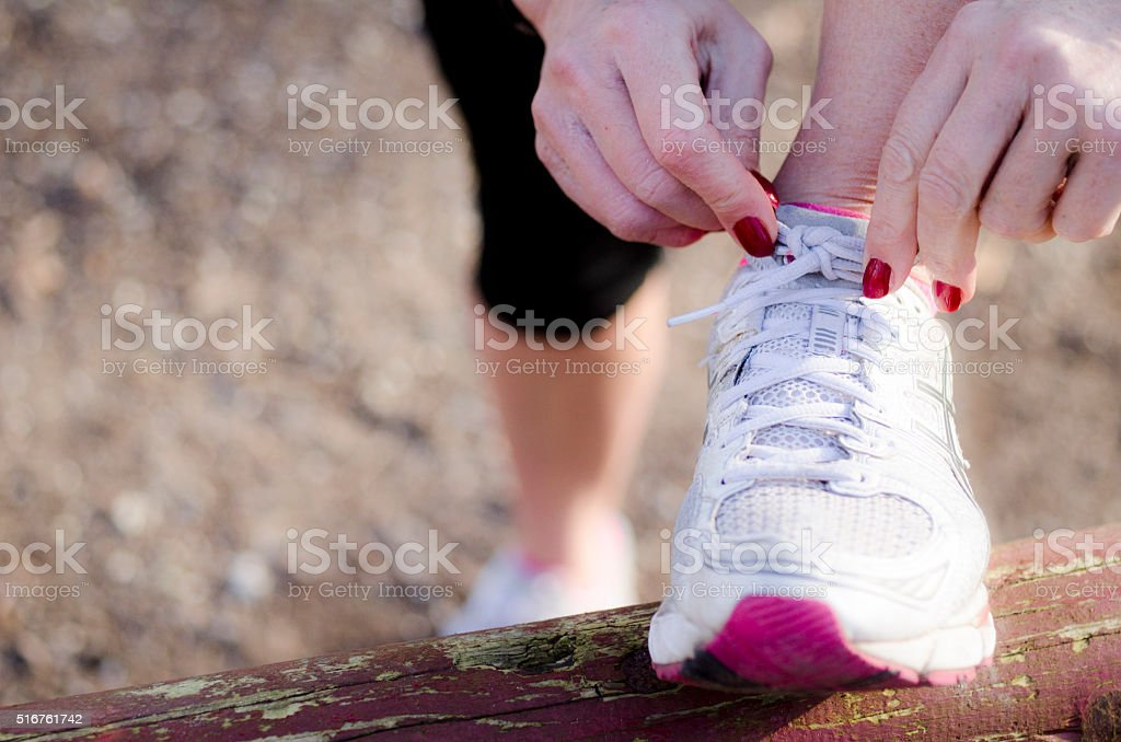 Woman tying her sports shoe in the morninglight stock photo