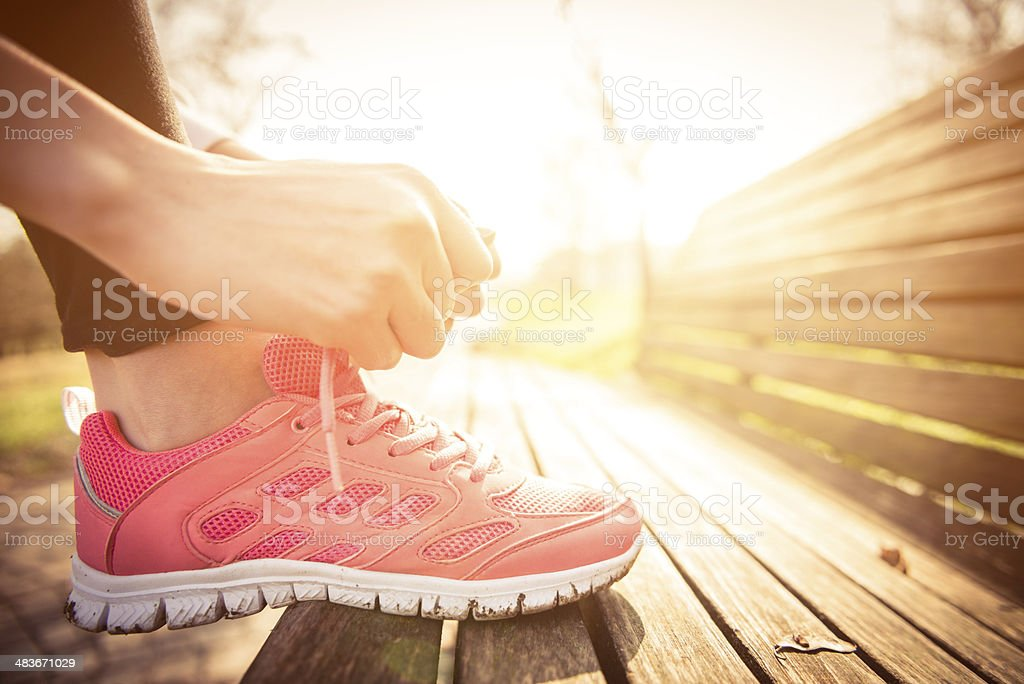 Woman tying jogging shoes stock photo