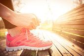 Woman tying jogging shoes