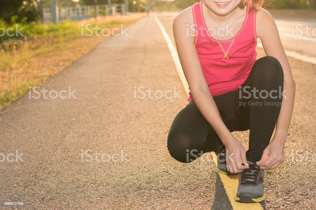 Woman tying shoe before running in sunny nature stock photo