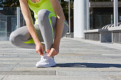 Woman tying shoelaces before running outdoor in the city