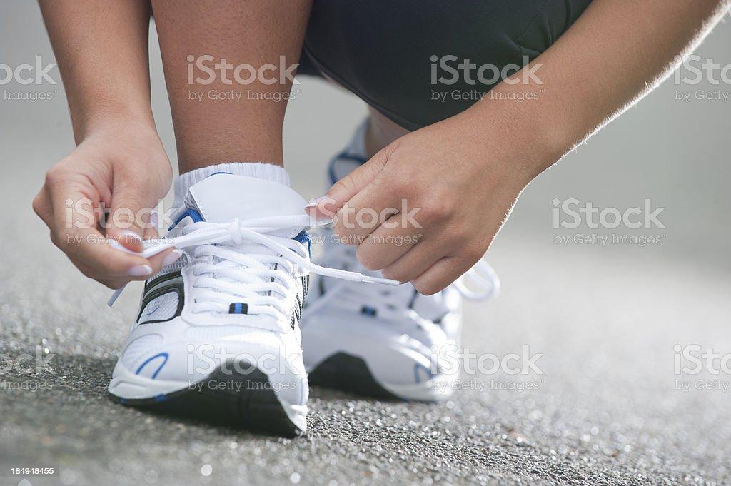 Woman tying shoelaces stock photo
