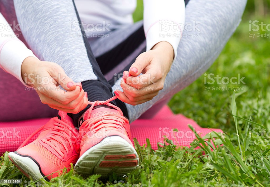 Woman tying sneakers on grass stock photo