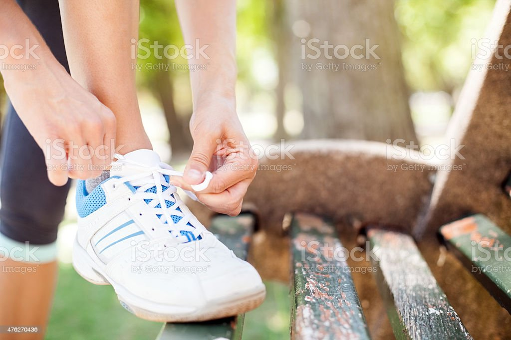 Woman Tying Sports Shoelace On Park Bench stock photo
