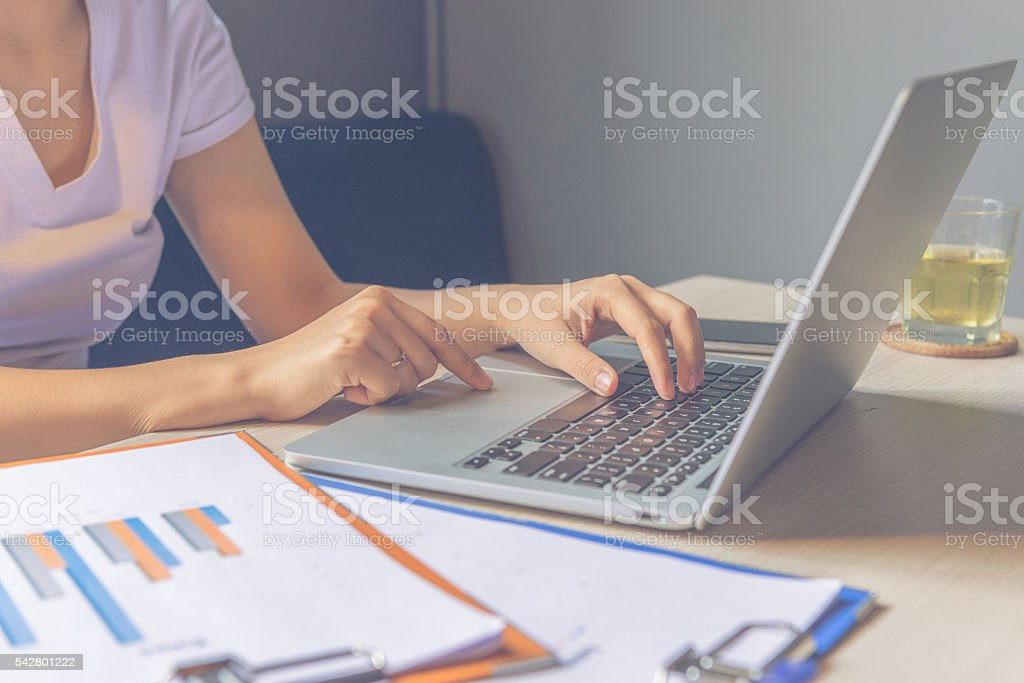 Woman typing laptop begins new working day in good mood stock photo