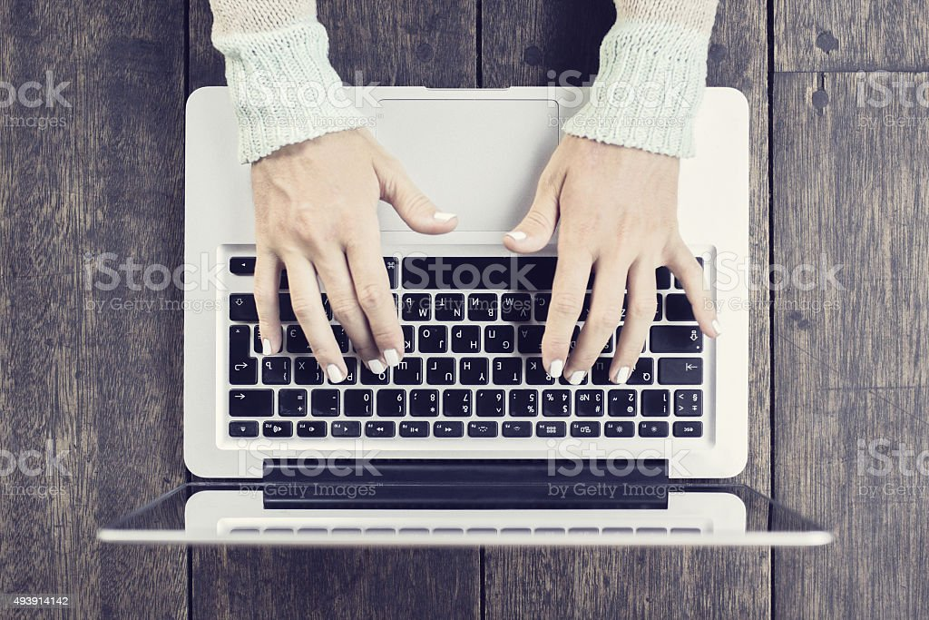 Woman typing on a laptop stock photo