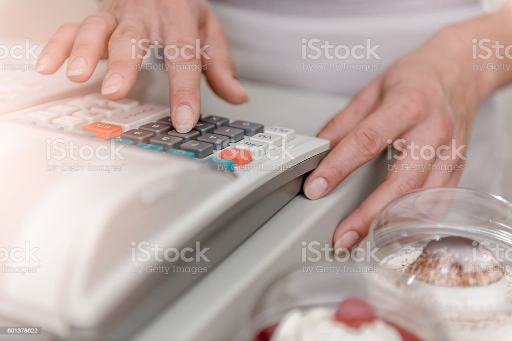 Woman typing on cash register stock photo