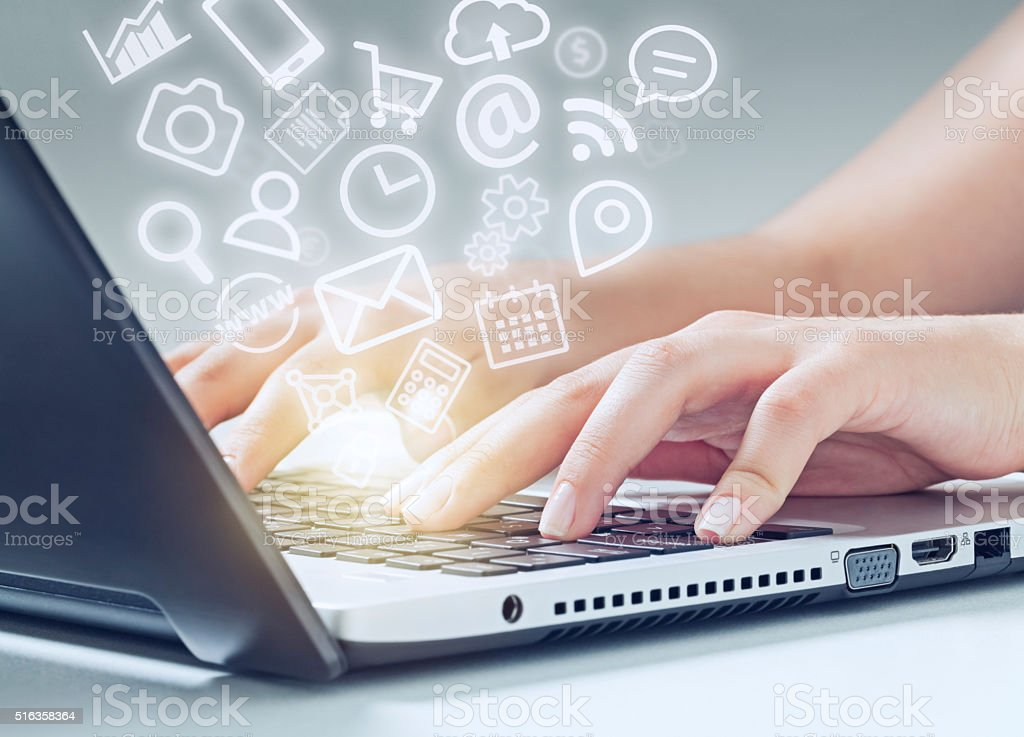 woman typing on laptop and media icons fly off stock photo