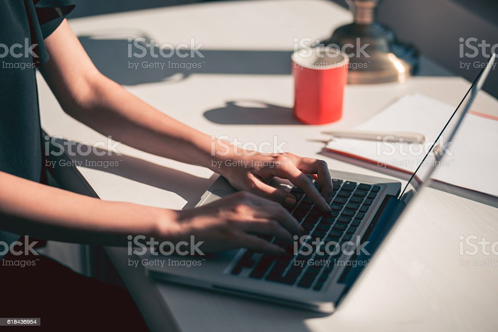 woman typing on laptop stock photo